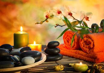 preparation for massage in orange lights and black stones - fototapety na wymiar