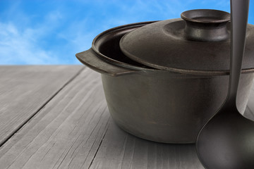 Cast iron cauldron with scoop on wooden table