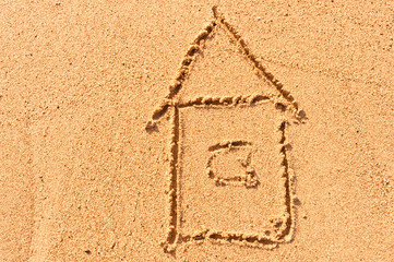 house drawing on the wet sand at the sea