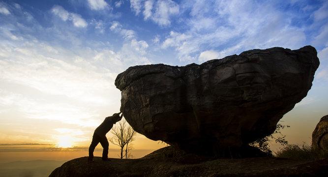 Man pushing a boulder on a rock