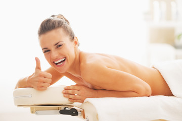 Smiling woman laying on massage table and showing thumbs up