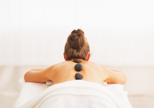 Young woman receiving hot stone massage. rear view
