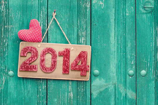 Vintage New Year date signboard ant heart on planks background