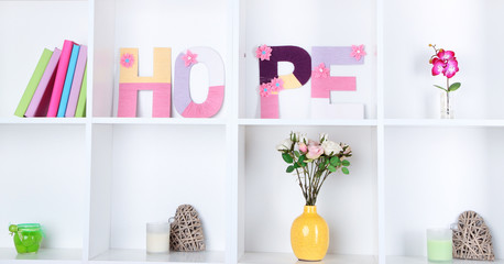 White shelves decorated with handmade knit word