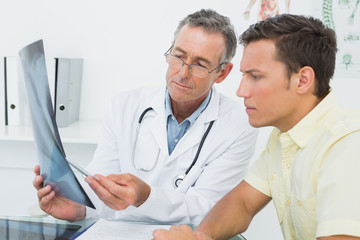 Doctor explaining lungs x-ray to patient in office