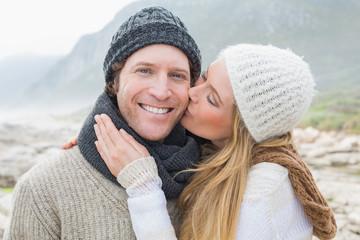 Woman kissing a man on rocky landscape
