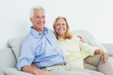 Happy loving senior couple sitting on sofa