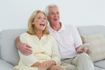 Cheerful senior couple with remote control at home