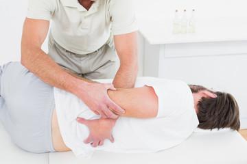 Male physiotherapist examining man's back