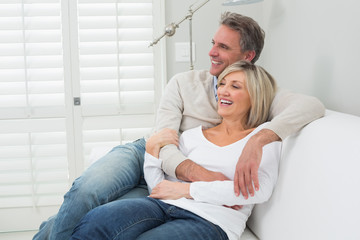 Happy couple embracing while sitting on sofa
