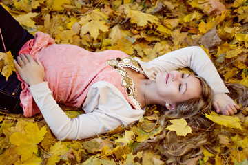 Beautiful happy pregnant woman lying with autumn leaves
