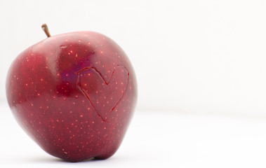 Red apple with an outline of a heart shape on it