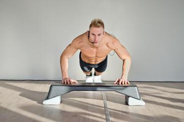 Young aerobics male coach on step teaching class