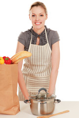Woman in apron with grocery bag , isolated on white background.