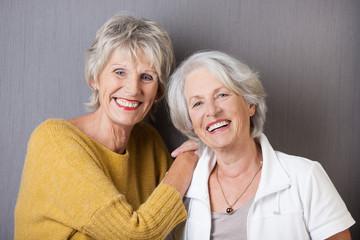 zwei ältere freundinnen vor grauer wand
