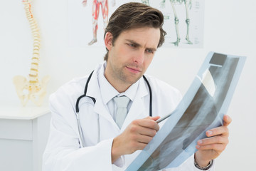 Concentrated male doctor looking at x-ray picture of spine