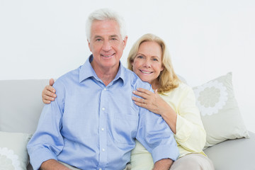 Relaxed loving senior couple sitting on sofa