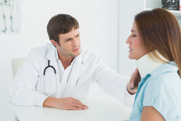 Doctor examining a patient's neck in medical office
