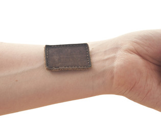 Blank leather label sewed on a hand isolated over white