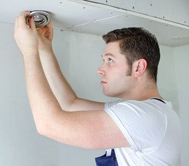 Certified electrician installing light bulb