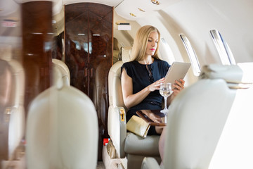 Woman Using Tablet Computer In Private Jet Wall mural