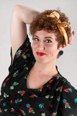 Pinup Girl in Flowered Smiles with Arm Over Head