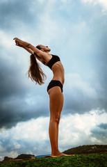 Beautiful slim woman makes yoga exercise