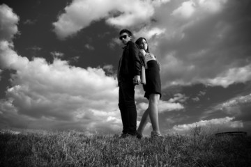 photo of sexy couple posing on top of hill back to back
