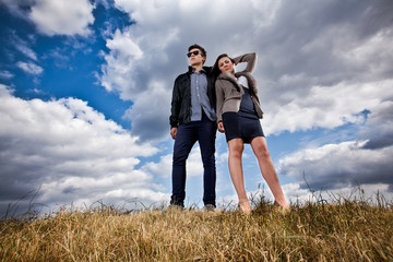 Young stylish couple posing on field against blue sky