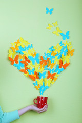 Paper butterflies fly out of cup on green wall background