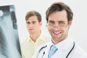 Smiling male doctor and patient examining lungs x-ray
