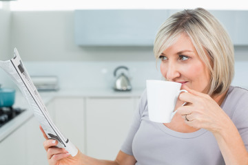 Woman drinking coffee while reading newspaper