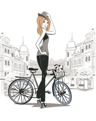 Fashion girl in a hat with a bicycle in the city