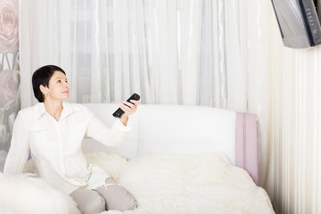 Woman watching television while lying on the bed