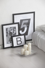 Closeup of a pictures and candles on a white bedroom.