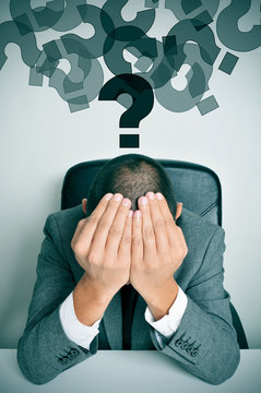 businessman with his hands in his head and question marks