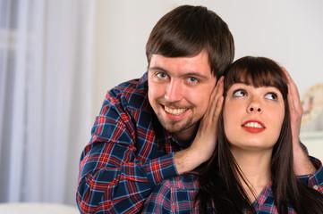 Young man close ears his girlfriend. Couple portrait