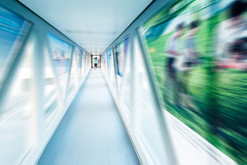 A long pedestrian tunnel, modern building interior.