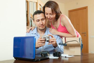 couple unpacking new compact digital camera