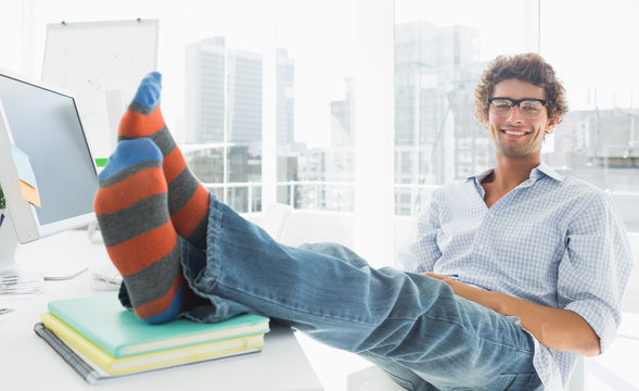 Relaxed casual man with legs on desk in office
