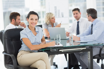 Young businesswoman with colleagues discussing in office