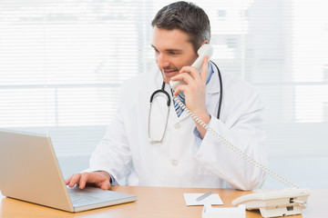 Concentrated doctor using laptop and phone