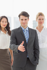 Businessman reaching hand out in front of his team
