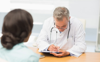 Doctor listening to his patient and taking notes