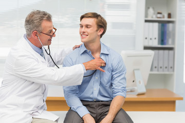 Mature doctor listening to his happy patients chest with stethos