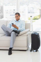 Businessman sending a text sitting on sofa waiting to depart on