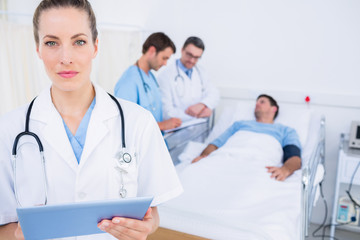 Doctor using digital tablet with colleagues and patient behind