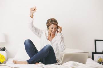 Mature businesswoman listening music on the bed.