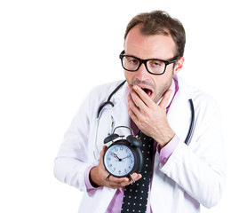 Exhausted, sleepy, tired doctor holding alarm clock