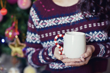 young pretty woman under new year tree with christmas cup of tea